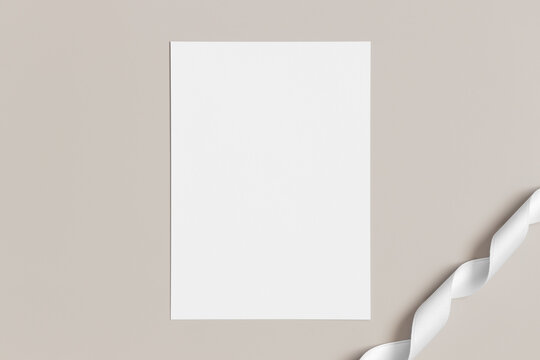 White invitation card mockup with a satin tape on a beige background. 5x7 ratio, similar to A6, A5.