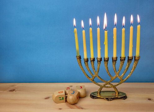 Hanukkah menorah with burning candles and wooden dreidels.  (Hebrew letters on color dreidels say : Great Miracle Happened Here.)