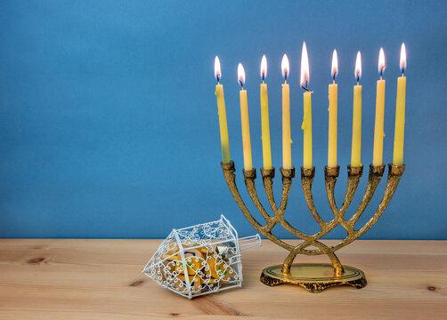 Hanukkah menorah with burning candles and wooden dreidels.