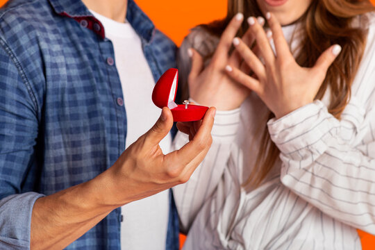Focus on box with ring in strong male hand and excited gestures of happy and surprised woman