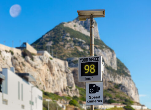 A traffic sign in Gibraltar warns of speed cameras. The real speed is shown on a display. In the background out of focus with bokeh is the Rock of Gibraltar with the moon in the sky.