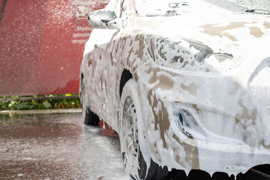 Beige passenger car in soapy foam at a car wash service, horizontal transport