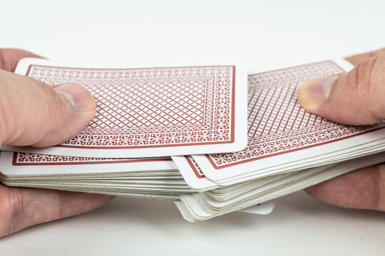 Hands shuffling playing cards on white background