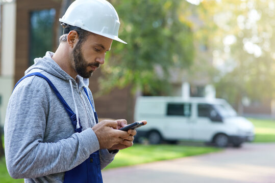Young male builder in hardhat using smartphone, standing outdoors while working at cottage construction site