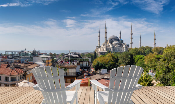 Beautiful view of Istanbul old town with Sultanahmet Mosque (Blue Mosque)  at sunny day from top terrace with white chairs, Istanbul, Turkey.