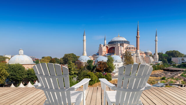 Beautiful view of Istanbul old town with world famous Hagia Sophia at sunny day from top terrace with white chairs, Istanbul, Turkey.