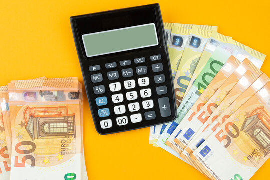 above view of stacks of Euro bills and calculator on orange background, saving or spending money concept