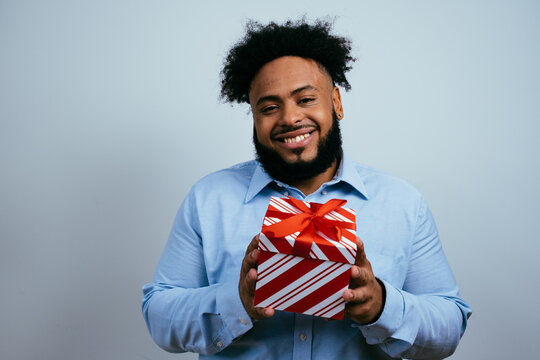Portrait of a smiling young man smiling and holding red Christmas gift box present.