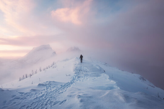 Man mountaineer walking with footprint on snowy mountain and colorful sky in blizzard at sunrise
