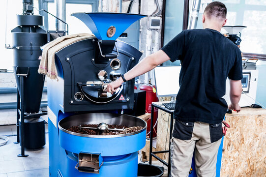Coffee pouring from roaster machine to cooling cylinder.