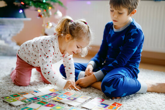 Two little chilren, cute toddler girl and school kid boy playing together card game by decorated Christmas tree. Happy healthy siblings, brother and sister having fun together. Family celebrating xmas
