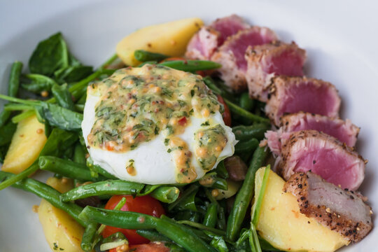 Warm salad with tuna, poached egg, cherry tomatoes, spinach, green beans on plate. Fresh food close-up