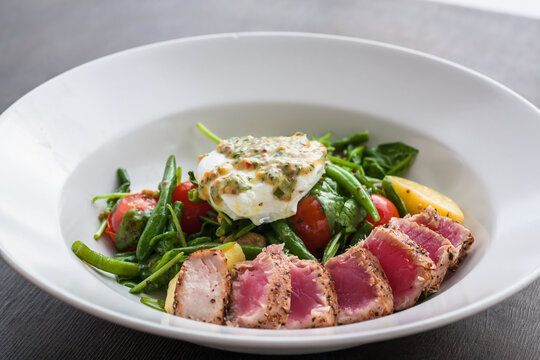 Fresh food in restaurant plate with salad and tuna. And, poached egg, spinach, green beans in meal. Fresh food close-up