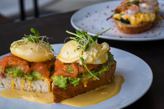 Plates and fresh toasts with salmon, guacamole, poached egg, with sauce. Fresh food close-up