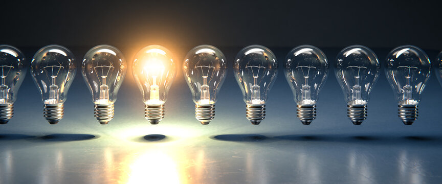 A row of lightbulbs with one brigthly lit - concept for having an idea, innovation, standing out. Web banner size
