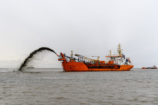 Vessel engaged in dredging. Dredger working at sea. Ship excavating material from a water environment.