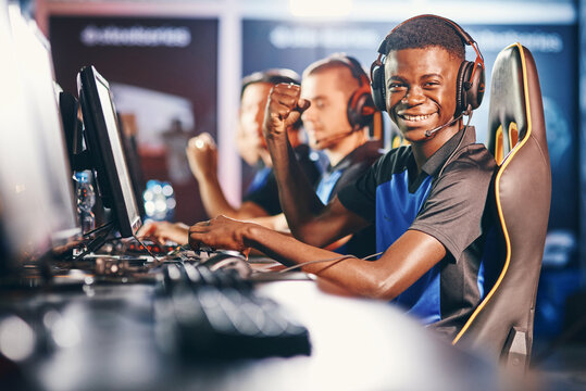 Side view of a cheerful african guy, professional cybersport gamer wearing headphones looking at camera and smiling while participating with team in eSport tournament