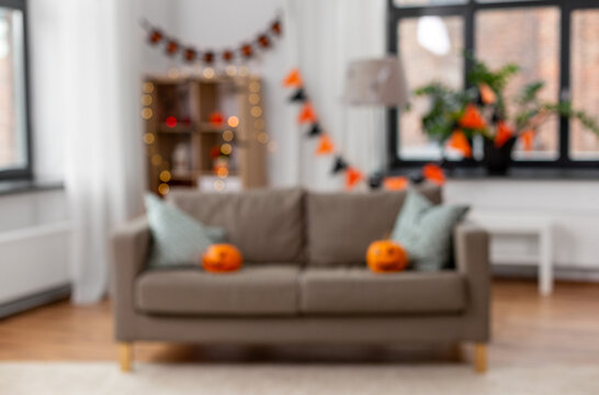 holidays, decoration and party concept - blurred home room with jack-o-lanterns or pumpkins on sofa and halloween decorations