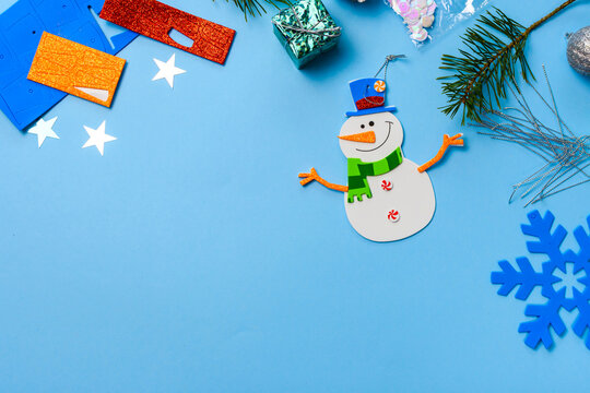 Christmas tree hanging ornaments. Snowman parts on blue wooden background. Christmas crafts ideas. Top view. space for text.