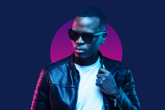 Neon portrait of african american man, wearing sunglasses and leather jacket, isolated on blue background