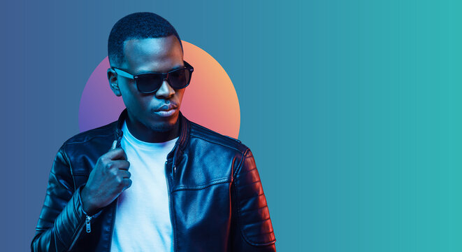 Banner of stylish black young man wearing leather jacket and sunglasses, isolated on blue gradient background