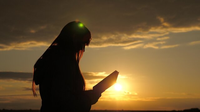 A woman reads a book in rays of the sun. Man reads Bible outdoors. A man holds the Bible in his hands and studies the word of God at sunrise on top of mountain. Searching for truth in scriptures.