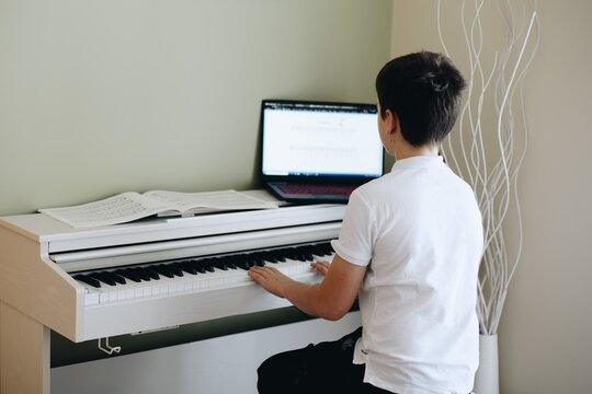 Young boy playing with music notes on the white piano looks at the laptop.
