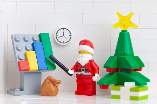 Tambov, Russian Federation - November 2, 2020 Lego minifigure Santa Claus pointing out company growth on a chart.