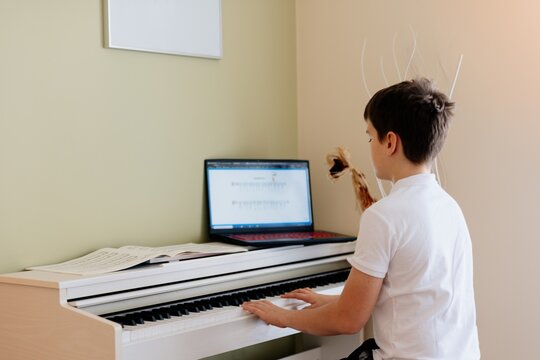 A young boy playing with sheet music on a white piano.