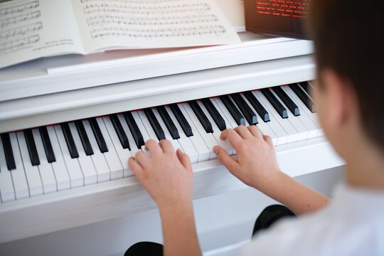 Hands of a boy playing the piano with sheet music.
