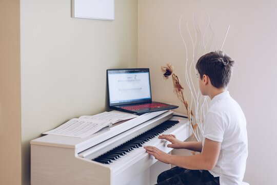 12 year old boy playing the white piano looking at the notes of his laptop.
