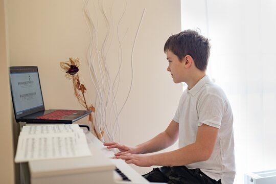 A young boy is learning to play the white digital piano, he looks at the sheet music in his laptop.