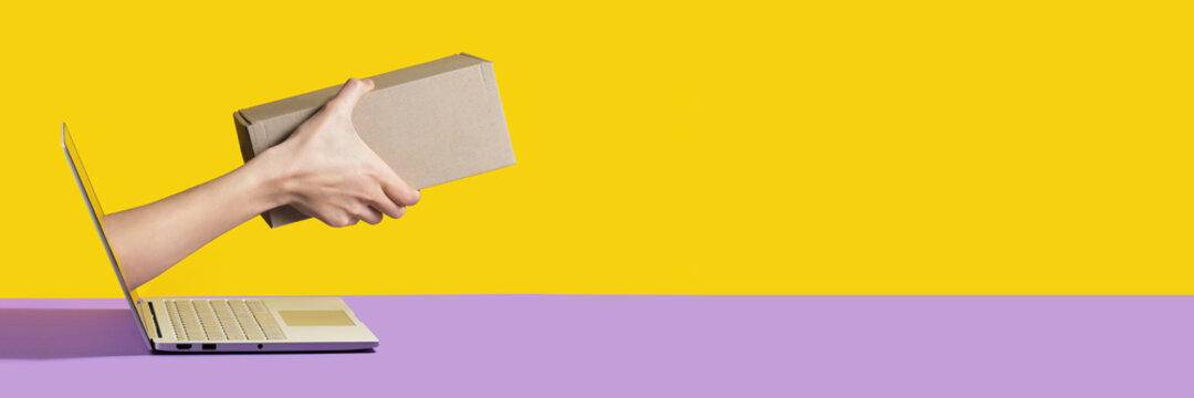 Giving a delivery package or a gift from the screen of the computer online yellow and purple background