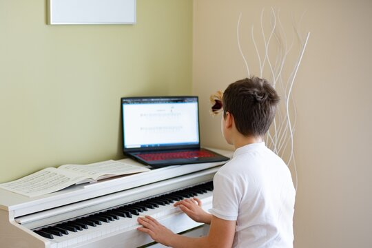 Young boy playing the white digital piano looking at the notes in the laptop.