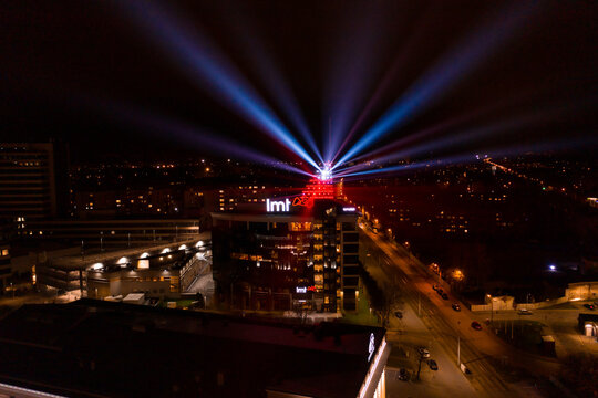 "Riga, Latvia, 11.18.2020. Light festival ""Staro Riga"". Latvian LMT building glowing in lights and light beams creating a festive atmosphere. Modern architecture in vivid lights near VEF."