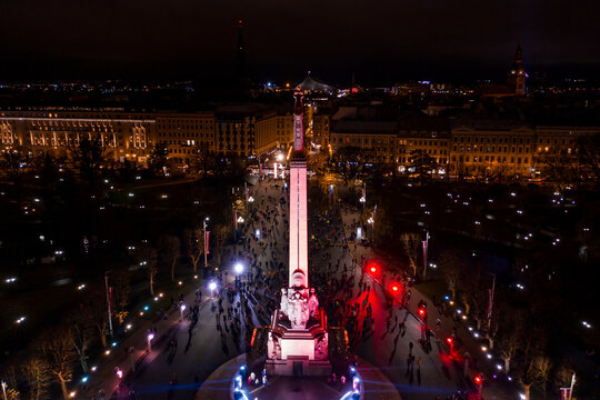 Riga,Latvia - 18 November 2020: Monument of freedom at night in Riga, Latvia during Staro Riga event. Milda - Statue of liberty holding three stars over the city illuminated in different colors.