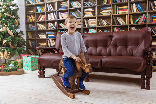 Happy young boy on wooden rocking horse, with Christmas tree in background