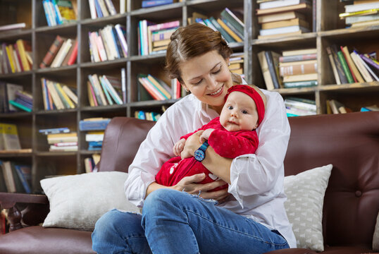 Young woman and her baby daughter on couch in library
