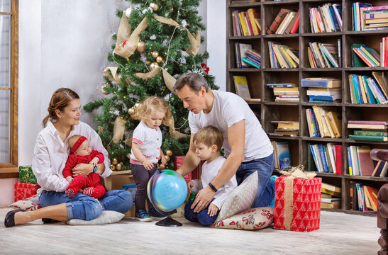 Family with three children beside Christmas tree at home. Kids and father examining globe, mom is holding baby girl.