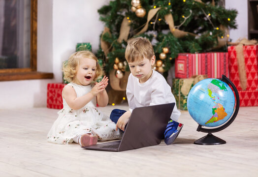 Young girl and boy watching something on laptop computer beside Christmas tree. Globe next to kids.
