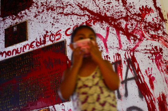 A girl adjusts her mask while standing in front of a monument painted in red during a protest to mark the International Day for the Elimination of Violence against Women, in San Salvador