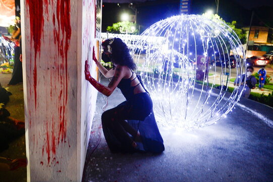 A woman puts her hands with red paint on a monument during a protest to mark the International Day for the Elimination of Violence against Women, in San Salvador
