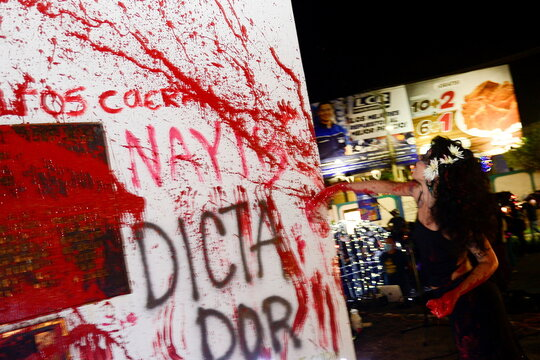 A woman throws red paint to a monument during a protest to mark the International Day for the Elimination of Violence against Women, in San Salvador