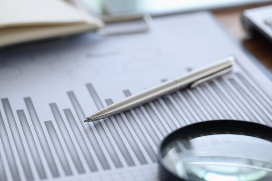 Ballpoint pen and magnifying glass lying on documents with graph in office closeup. Dynamics of economic development concept