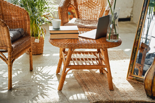 Simple and soft living room in daytime with bamboo armchairs and table with books and laptop on it.