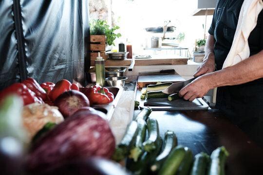 Koch bei der Arbeit am Gemüse schneiden und kochen
