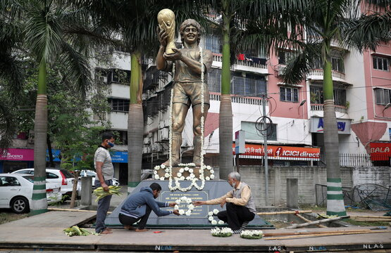 People decorate a statue of Argentine soccer great Diego Maradona before a prayer meeting, in Kolkata