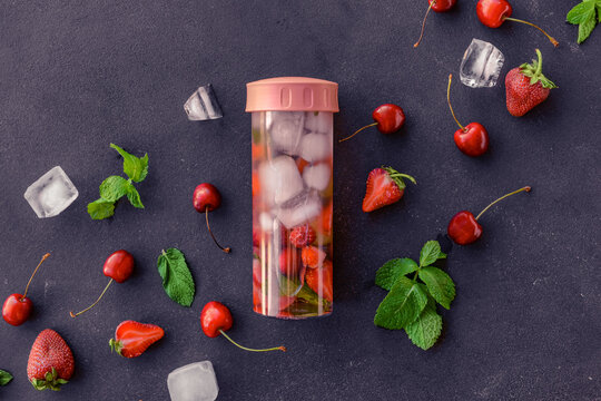 Bottle of mint infused water with berries on dark background