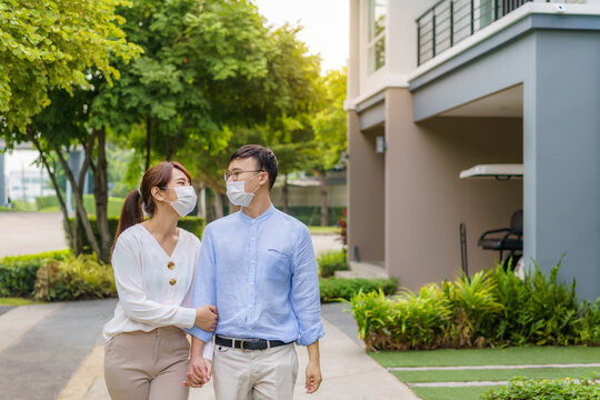 Asian couples with protective masks walking in pathway in public park at village together during the Coronavirus epidemic.