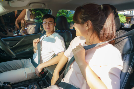 Young couple fasten seat belts in their brand-new auto before roadtrip journey for safety.